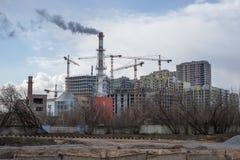 Costruzioni di appartamento alte in costruzione con la gru contro la a Fotografie Stock