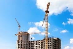 Costruzioni di appartamento alte in costruzione con le gru contro Fotografia Stock Libera da Diritti