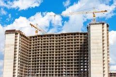 Costruzioni di appartamento alte in costruzione con le gru contro Fotografie Stock Libere da Diritti