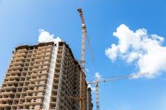 Costruzioni di appartamento alte in costruzione con le gru contro Fotografia Stock