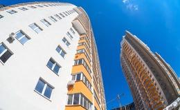 Costruzioni di appartamento alte in costruzione contro un cielo blu b Immagine Stock