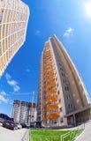 Costruzioni di appartamento alte in costruzione contro un cielo blu b Immagine Stock Libera da Diritti