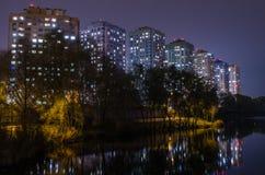 Costruzioni di appartamento con le finestre d'ardore vicino allo stagno alla notte fotografie stock