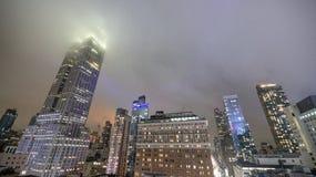 Costruzioni di New York alla notte con nebbia fotografia stock