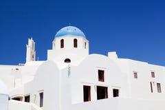 Costruzioni e chiesa con la cupola blu a OIA o Ia bianca sull'isola di Santorini, Grecia Immagine Stock