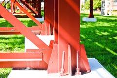 Costruzioni metalliche rosse, contributi della ruota ai tubi, cavalletto della conduttura dai grandi fasci, mucchi e rinforzi all fotografia stock libera da diritti