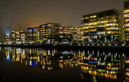Costruzioni moderne riflesse in acqua alla notte Fotografia Stock Libera da Diritti