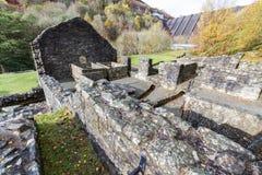 Costruzioni rovinate della miniera di piombo con la diga nella distanza Immagine Stock