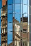 Costruzioni storiche riflesse nell'architettura di vetro moderna immagini stock