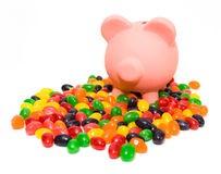 Costs of Candy. Concept with jelly beans and a piggy bank on white background Stock Photos
