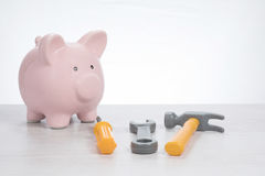 Costs of doing home renovations. Or maintenance with a pink piggy bank alongside a hammer, screwdriver and hammer in a DIY concept Royalty Free Stock Images