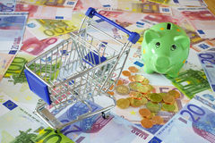 Costs of Living. Blue shopping cart and a green piggy bank on background made of euro banknotes and coins Royalty Free Stock Photo