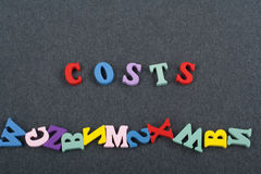 Costs word on black board background composed from colorful abc alphabet block wooden letters, copy space for ad text. Learning english concept stock image