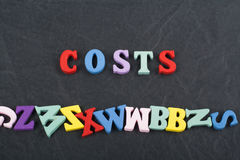 Costs word on black board background composed from colorful abc alphabet block wooden letters, copy space for ad text Royalty Free Stock Images