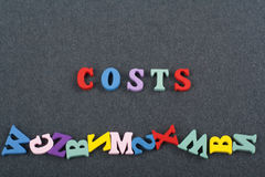Costs word on black board background composed from colorful abc alphabet block wooden letters, copy space for ad text Royalty Free Stock Image