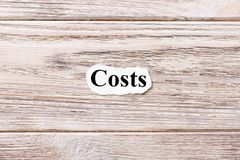 Costs of the word on paper. concept. Words of costs on a wooden background Royalty Free Stock Photo