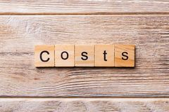 Costs word written on wood block. costs text on wooden table for your desing, concept.  royalty free stock photography
