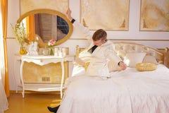 Costume blanc de port de type de jeune adolescent et mensonge sur le lit dans sa pièce d'or, étirage et baîllement image stock