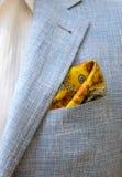 Costume bleu avec une chemise blanche et avec une écharpe jaune dans une poche Photographie stock libre de droits