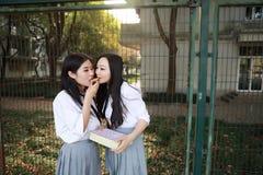 Costume chinois asiatique d'étudiant d'usage de deux le beau joli filles dans des meilleurs amis d'école sourient biscuit de cass Image libre de droits