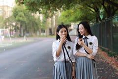 Costume chinois asiatique d'étudiant d'usage de deux le beau joli filles dans des meilleurs amis d'école sourient rire mangeant l Image stock