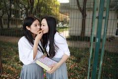 Costume chinois asiatique d'étudiant d'usage de deux le beau joli filles dans des meilleurs amis d'école sourient rire mangeant l Photographie stock libre de droits