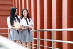 Costume chinois asiatique d'étudiant d'usage de deux le beau joli filles dans des meilleurs amis d'école sourient rire parlant et Image stock
