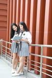 Costume chinois asiatique d'étudiant d'usage de deux le beau joli filles dans des meilleurs amis d'école sourient rire parlant et Images libres de droits