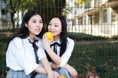 Costume chinois asiatique d'étudiant d'usage de deux le jeune joli filles dans des meilleurs amis d'école sourient fruit orange d Photos libres de droits
