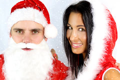 Costume christmas. Smiling young couple in santa clause costume stock images