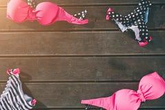 Costume da bagno delle donne che si trova sul fondo di legno Parte superiore ed inferiore di swimwear colorful Rosa e nero con le immagine stock
