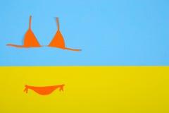 Costume da bagno di carta arancio del bikini su fondo blu e giallo mini Fotografia Stock Libera da Diritti
