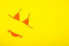 Costume da bagno di carta arancio del bikini su fondo giallo minimalistic Fotografia Stock