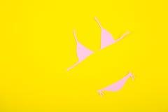Costume da bagno di carta rosa del bikini su fondo giallo Minimalistic Unione Sovietica Immagine Stock