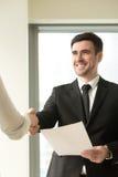 Costume de port de sourire heureux d'homme d'affaires serrant la main femelle, prise Images stock