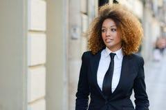 Costume de port et lien de femme d'affaires noire à l'arrière-plan urbain Photo libre de droits