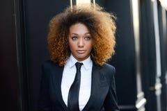 Costume de port et lien de femme d'affaires noire à l'arrière-plan urbain Photo stock