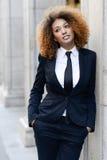 Costume de port et lien de femme d'affaires noire à l'arrière-plan urbain Photos stock