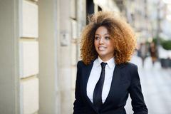 Costume de port et lien de femme d'affaires noire à l'arrière-plan urbain Images stock
