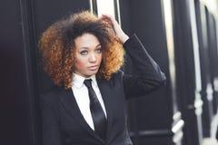 Costume de port et lien de femme d'affaires noire à l'arrière-plan urbain Image libre de droits