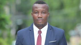 Costume de port de jeune homme d'affaires africain heureux dehors banque de vidéos