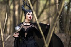 Costume Drama. Marvellous and Magical Maleficent Woman with Horns Posing in Spring Empty Forest with Crook. Horizontal Image Orientation royalty free stock images
