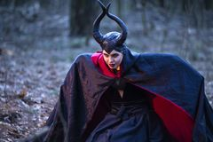 Costume Drama. Mysterious Maleficent Female Posing in Black Raincoat in Early Spring Forest royalty free stock photo