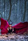 Costume Drama. Mysterious Maleficent Female Posing in Black Wavy Raincoat in Early Spring Forest stock photos