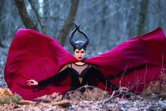 Costume Drama. Mysterious Maleficent Female Posing in Black Wavy Raincoat in Early Spring Forest royalty free stock photography