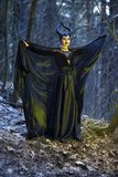 Costume Drama Play. Mysterious and Magical Maleficent Woman with Horns Posing in Spring Empty Forest with Wavy Shawl stock photo