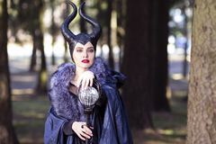 Costume Drama. Young caucasian Female Poses in Maleficent Clothing in Spring Forest stock photo