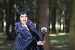 Costume Drama. Young caucasian Female Poses in Maleficent Clothing in Spring Forest. Horizontal Shot royalty free stock photography