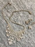 Costume jewerly. Necklace and earrings on stone royalty free stock image