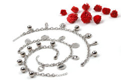 Costume jewerly and red flowers Royalty Free Stock Image